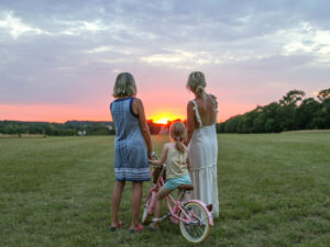 Two women and a child standing in Wild Meadow watching the sunset